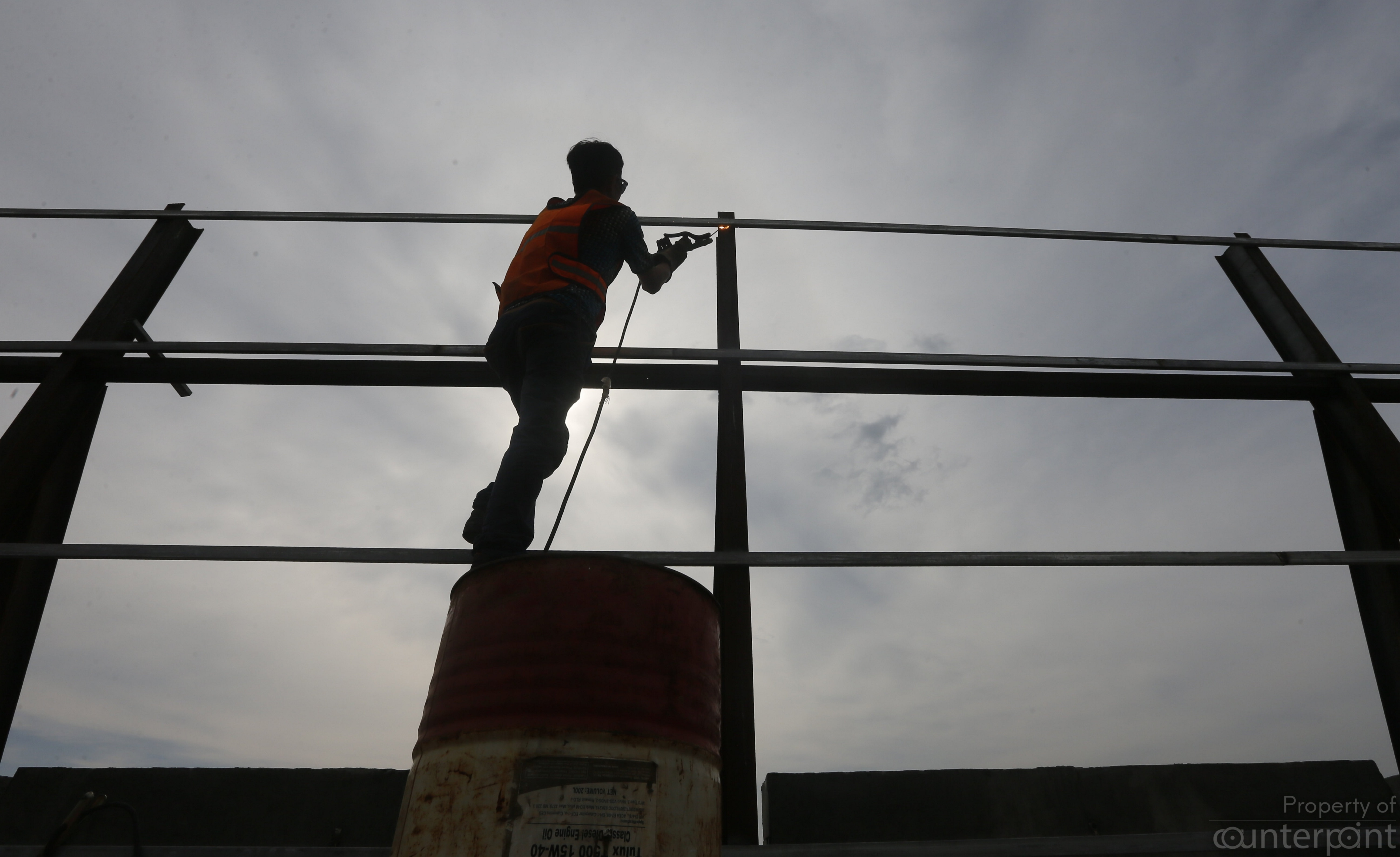 A welder hard at work as he balances on a barrel during the construction of the Colombo Port City in 2017.