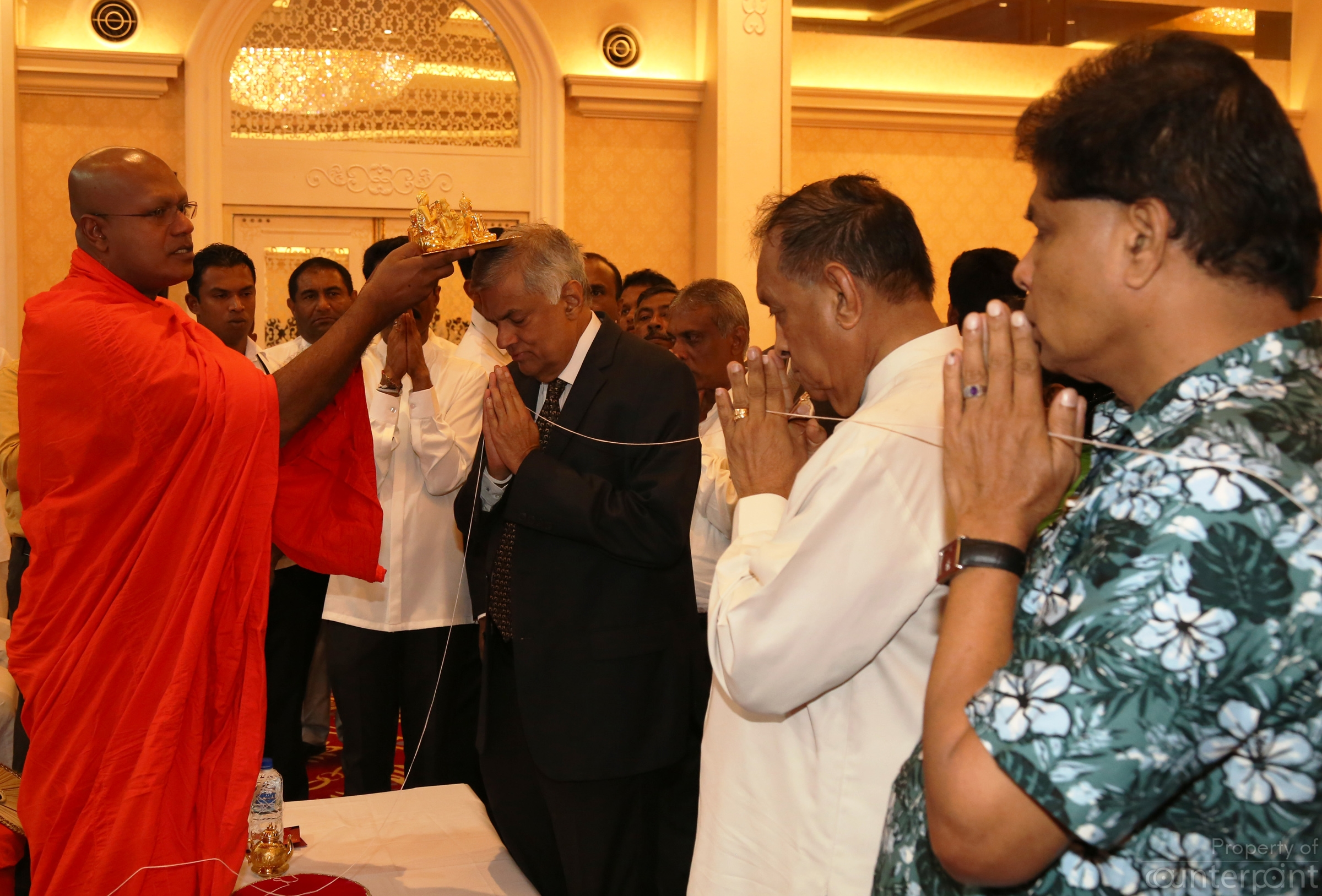 A large group of invitees including clergy of different religions attended a tea party at Temple Trees to mark the start of the New Year. Picture shows Prime Minister Ranil Wickremasinghe receiving blessings from a member of the Buddhist clergy. (PM's media unit)