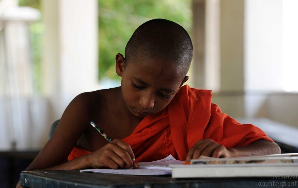 A student monk busy studying. Temple's are a rich source of ancient books and oral traditions where stories are told and re-told.