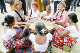 Tourists join village women in a round of traditional drumming.