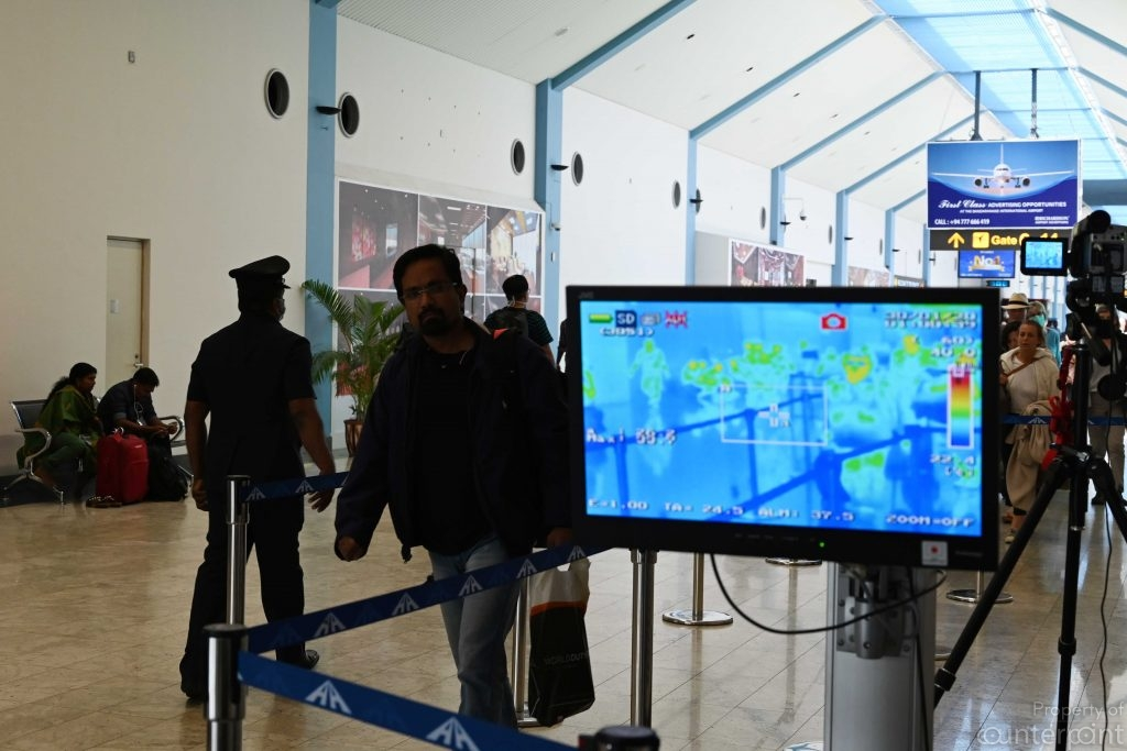 A thermal scanner set up at the Bandaranaike International Airport determines whether a passenger has a temperature.