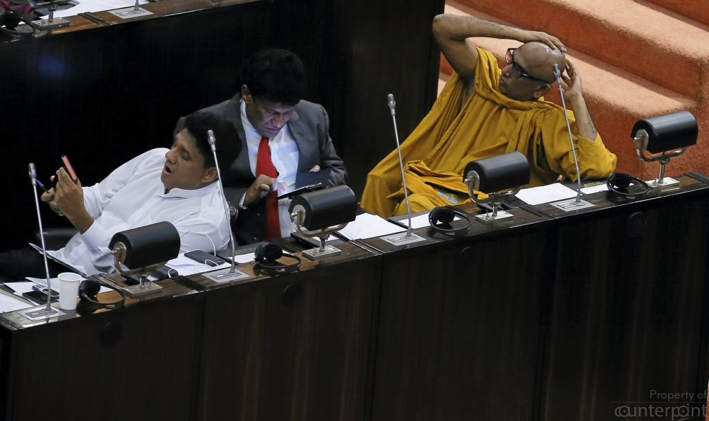 Bored: Ven. Athureliye Rathana seated with lay MPs in Parliament