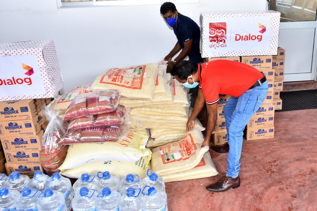 The teams from Dialog Axiata and TV Derana sorting through essential items prior to dispatching them to flood victims.